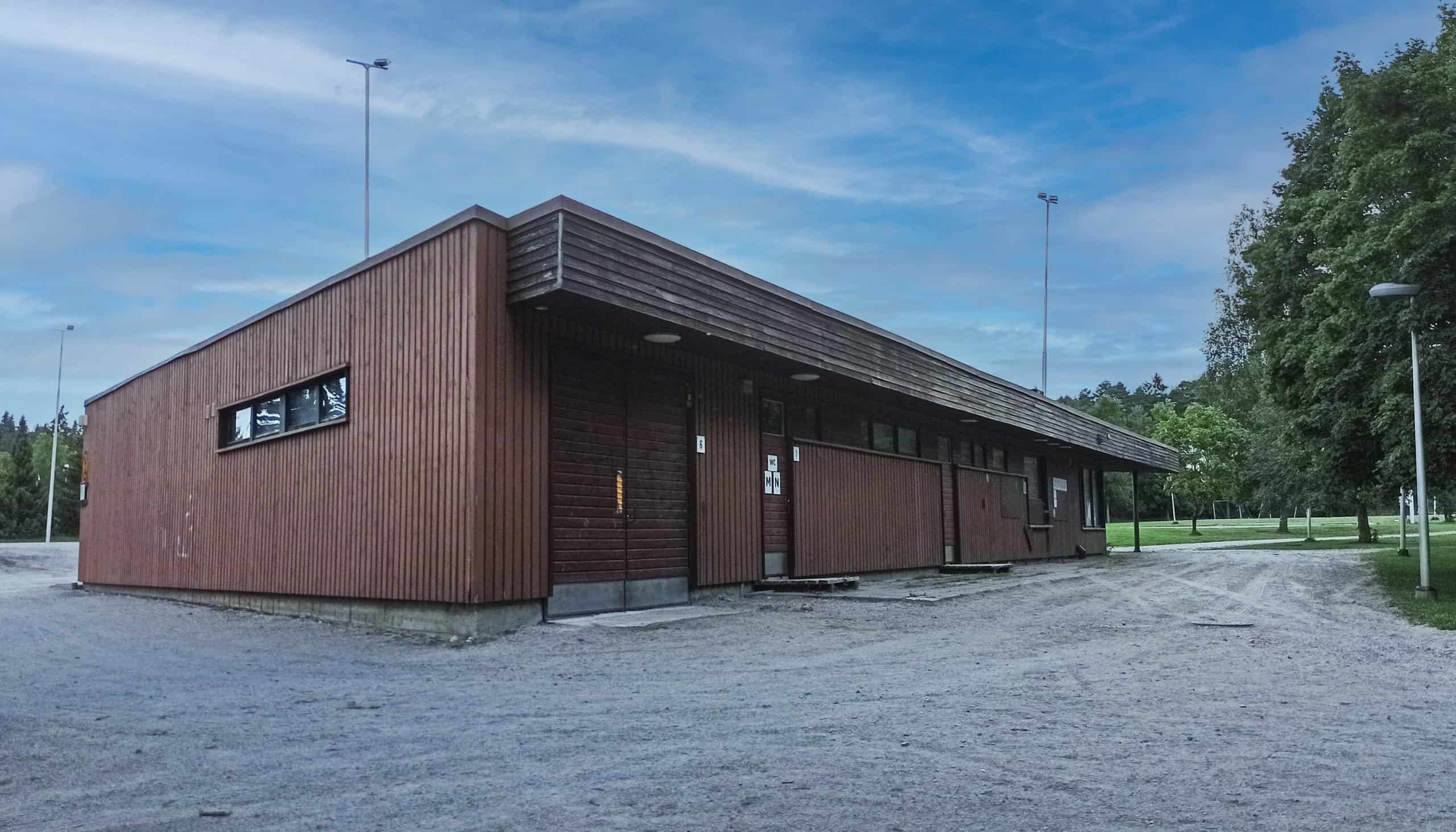 Ruskea rakennus jalkapallokentän reunalla.