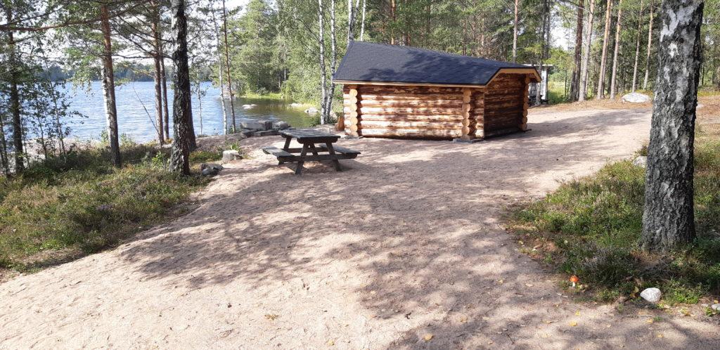Vasemmalla näkyy järvi, oikealla pieni rakennus.