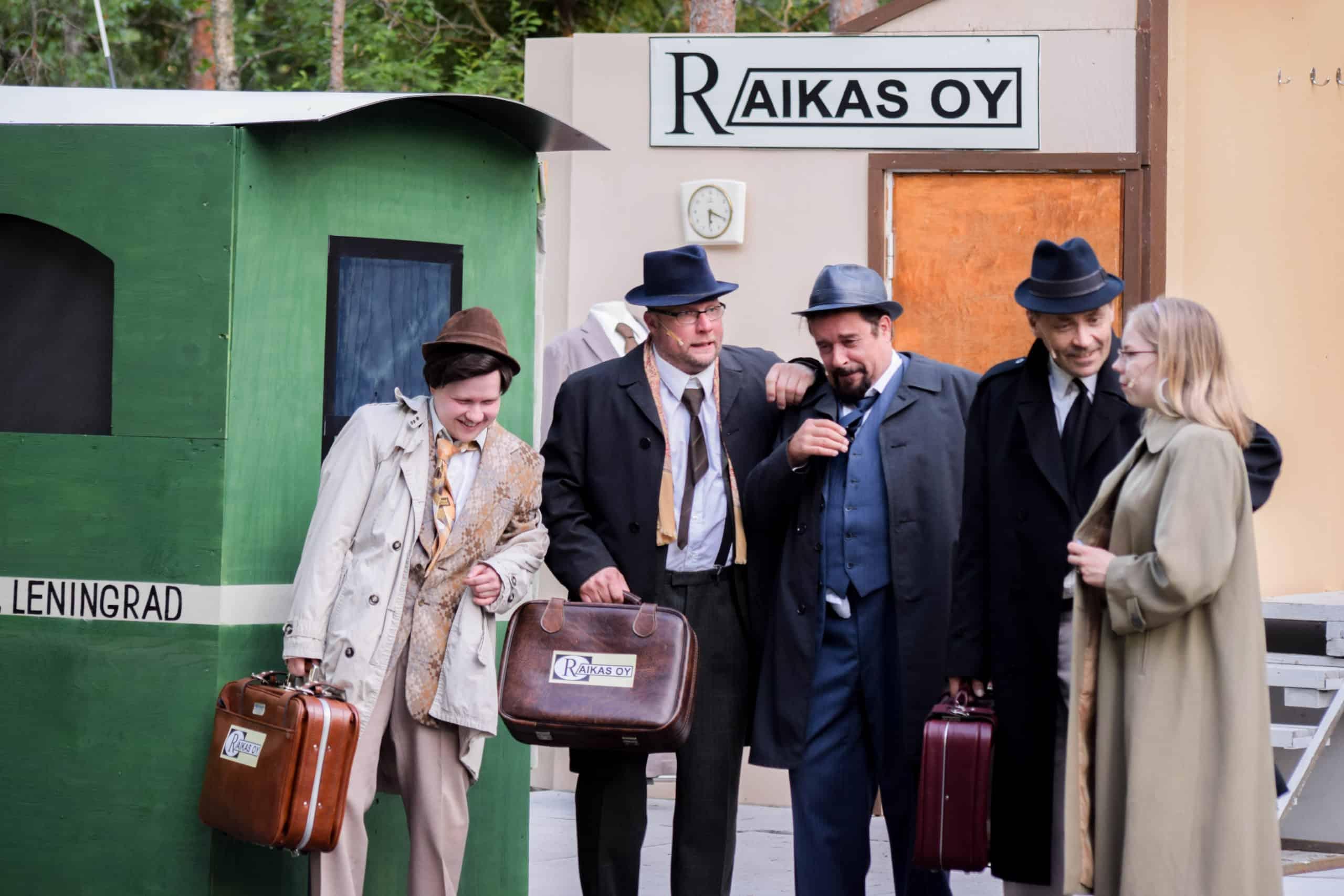 Humalaiset miehen nousevat junasta Raikas Oy:n salkkujen kera.