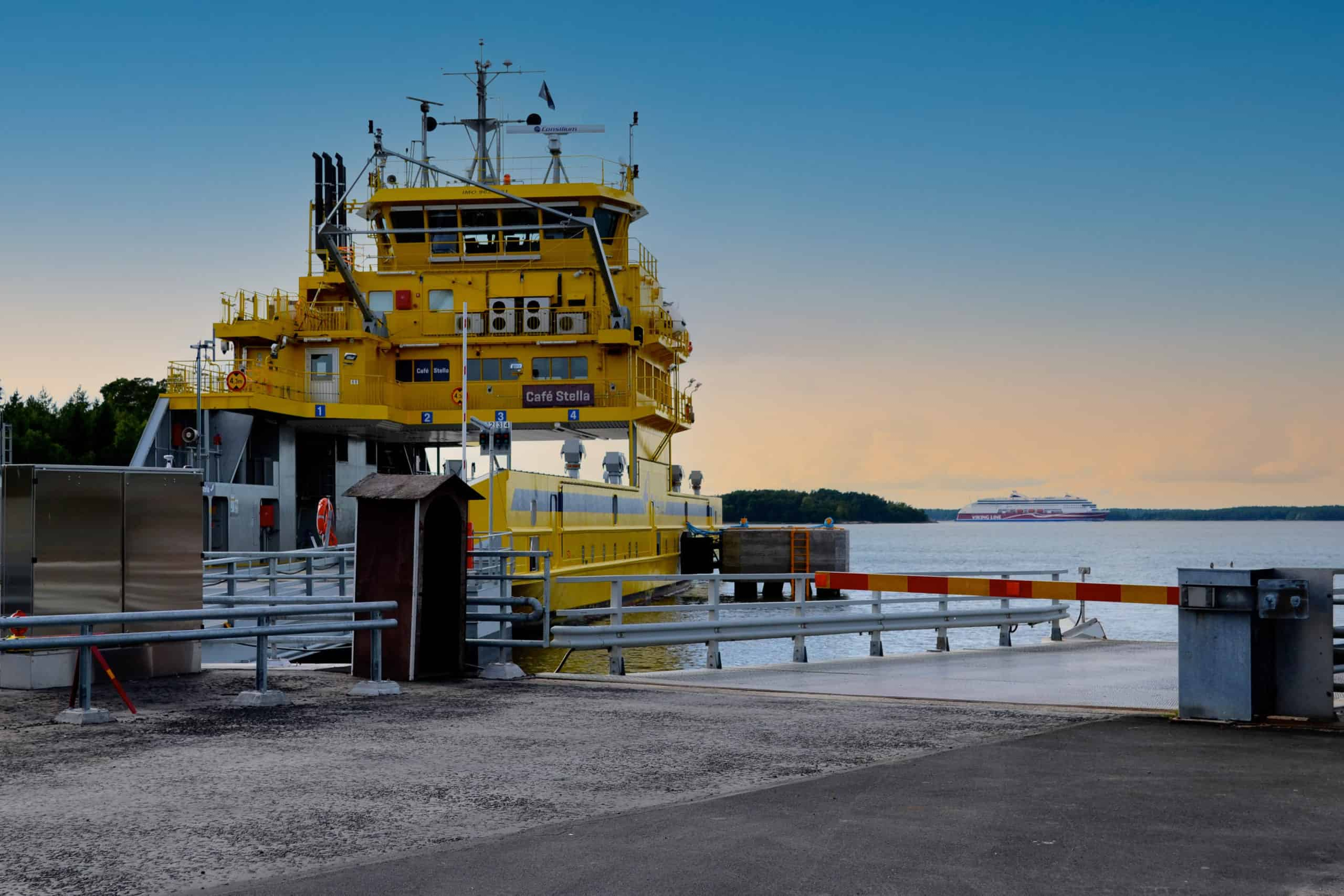 Keltainen lautta satamassa. Horisontissa risteilyalus.