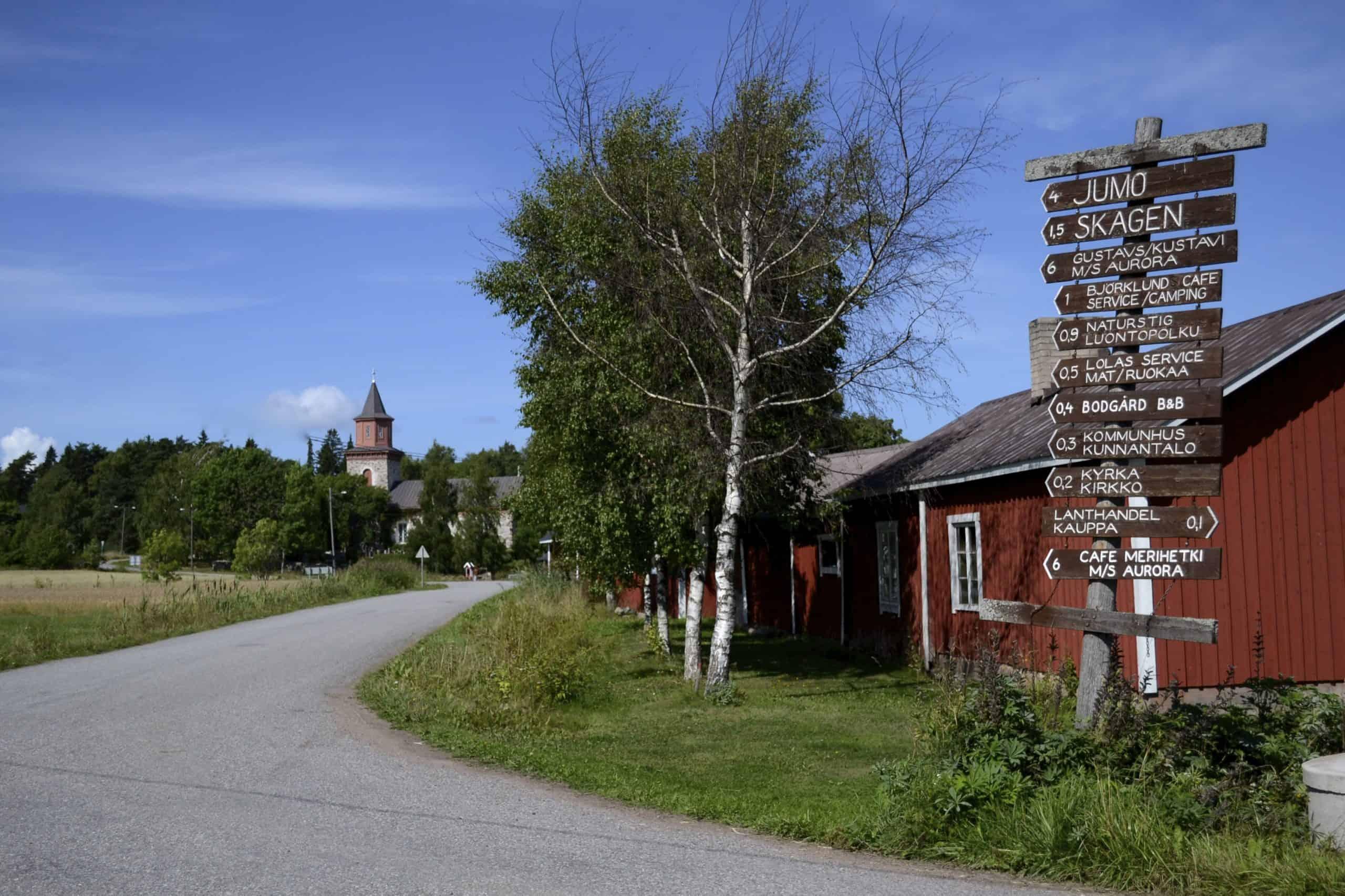 Iniön päätien varrella olevia kylttejä, punainen puurakennus ja taustalla kirkko.