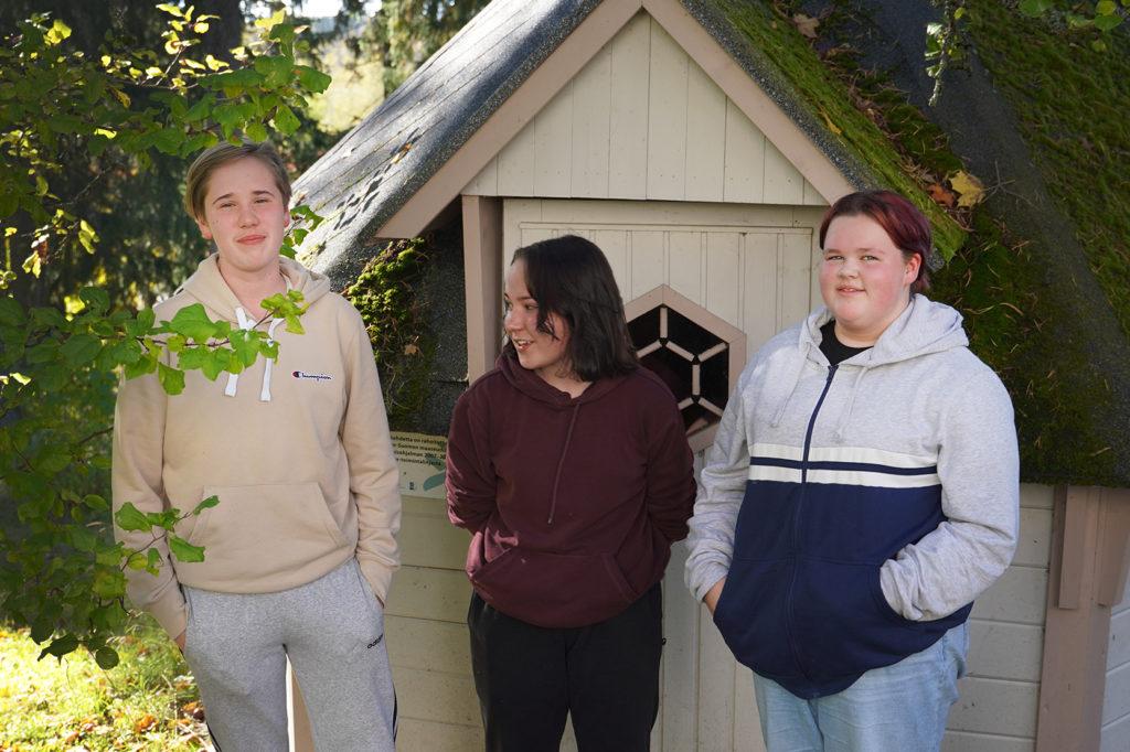Kolme nuorta seisoo vierekkäin ulkona kodan edessä.