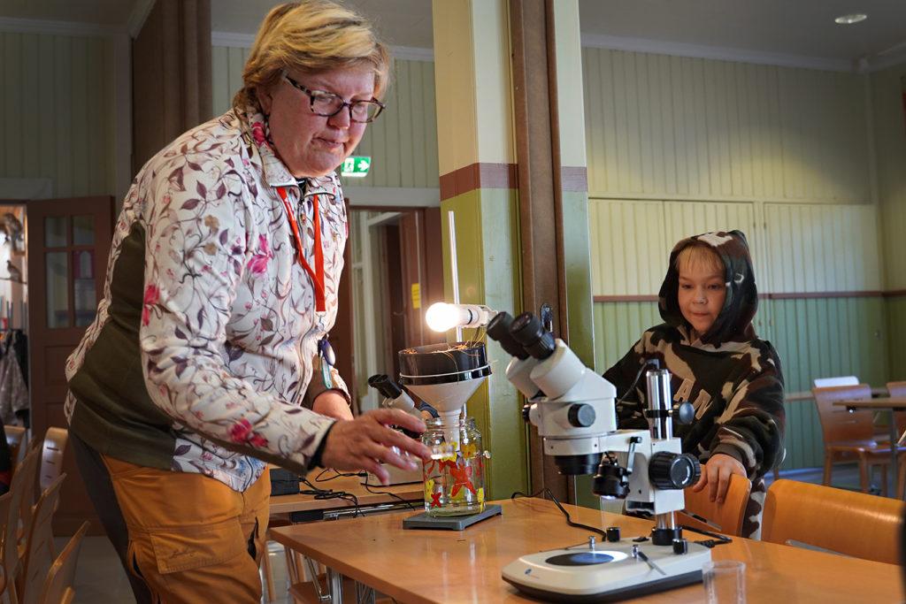 Nainen mikrokooppin äärellä ja poika katsoo taustalla.