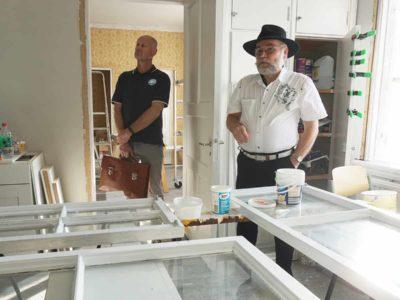 Kaksi henkilöä seisoo huoneessa, jossa ikkunankorjausprosessi on meneillään.