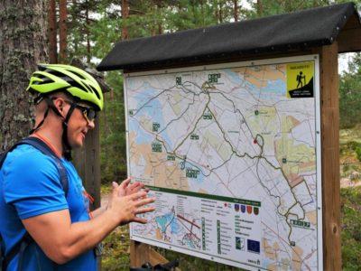 Pyöräilijä tarkastelee karttaopastetta.