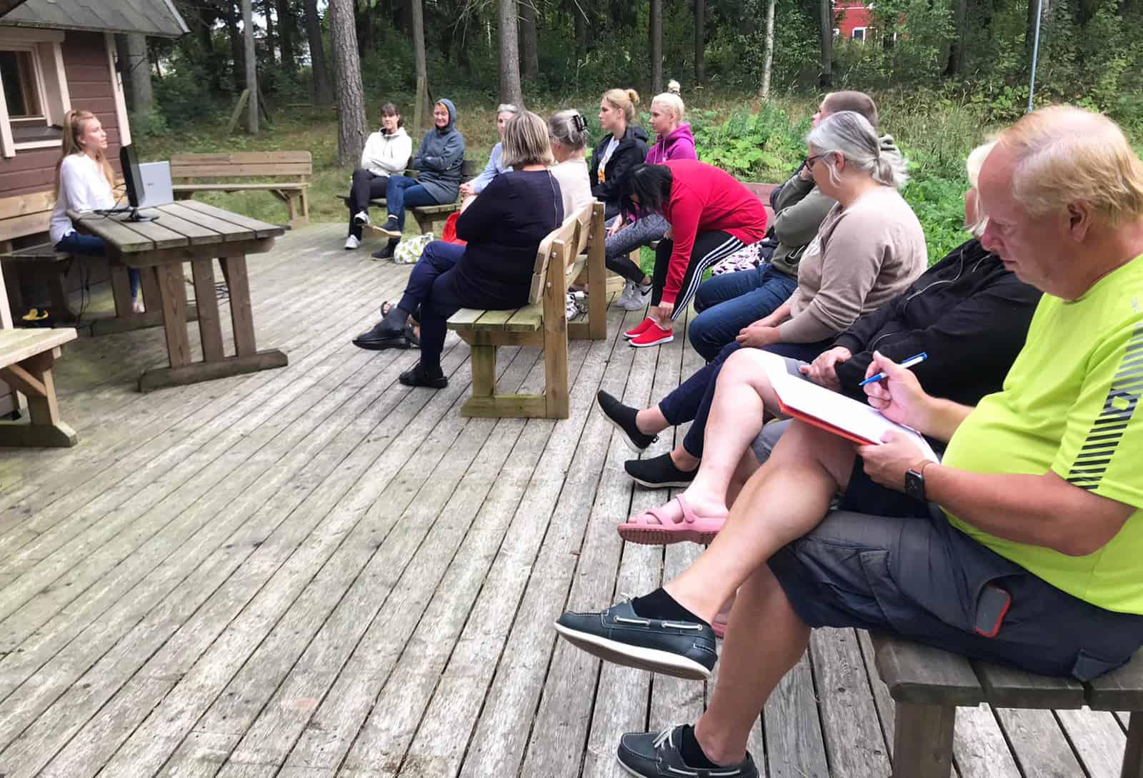 Ihmisiä istumassa kodan pihalla. Yksi luennoi, muut kuuntelevat.
