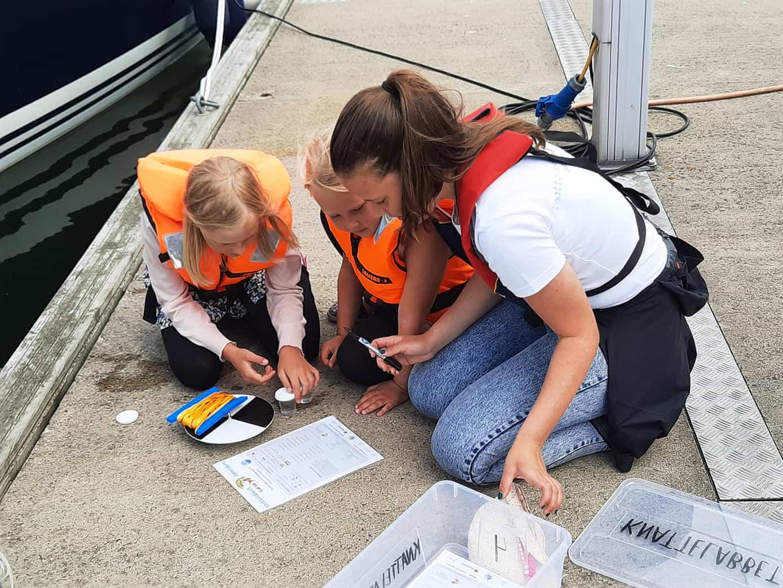 Lapsia tutkimassa merestä löytyneitä löydöksiä.