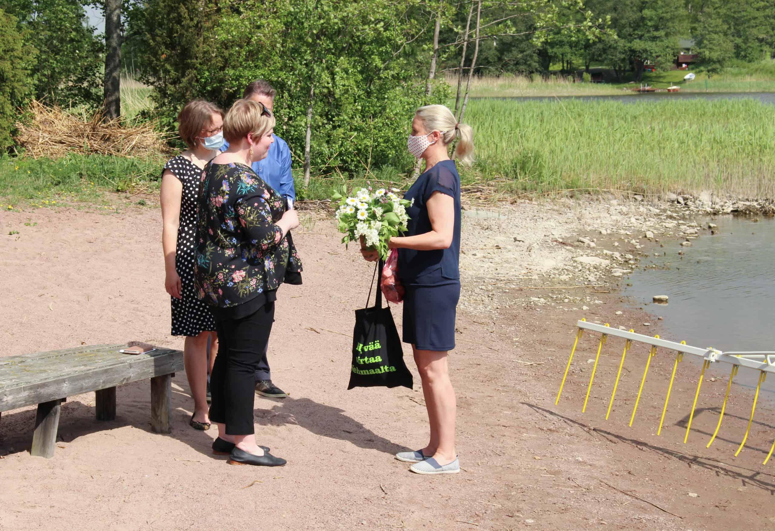 Anna Kaskinen luovuttaa ministeri Saarikolle paikallisia tuotteita rannalla.