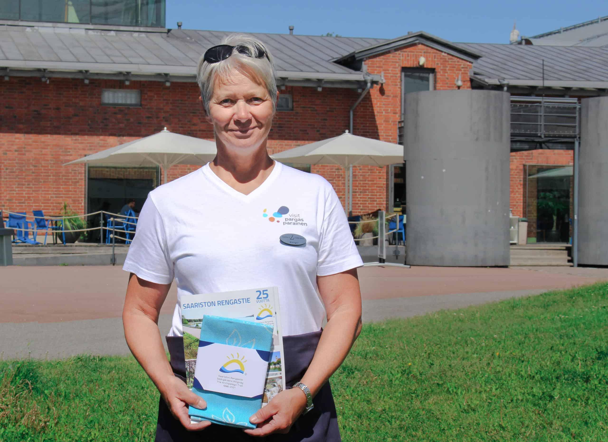 Margot Wikström esittelee keittiöpyyhettä ja uutta rengastien esitettä.