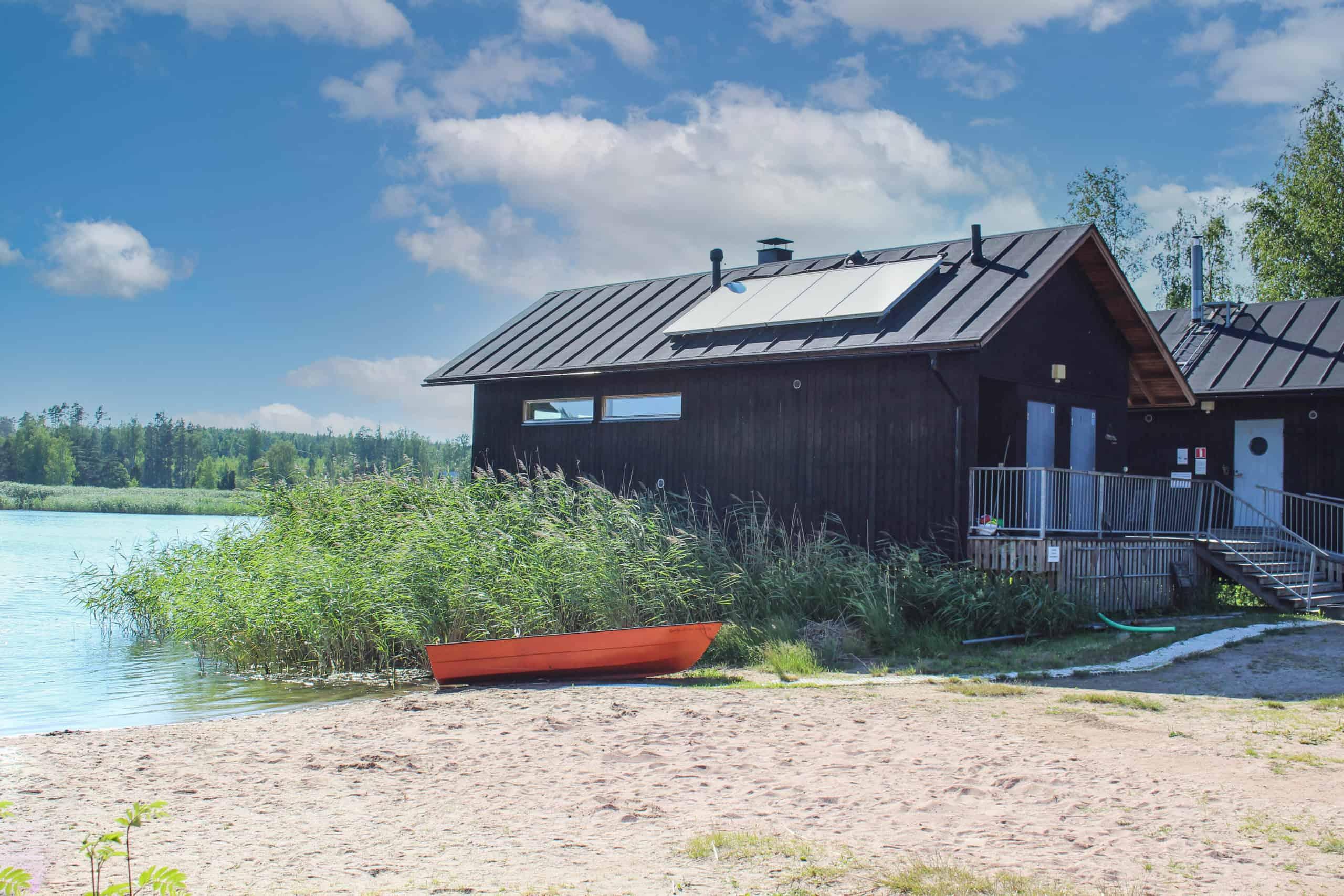Tumma rakennus ja punainen vene hiekkarannalla.