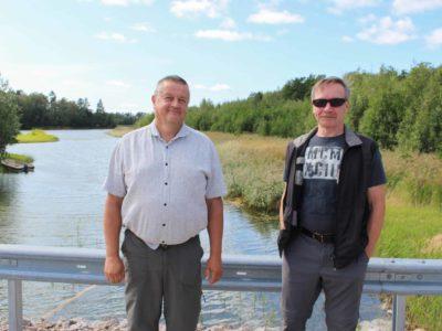 Kaksi miestä seisoo sillalla.