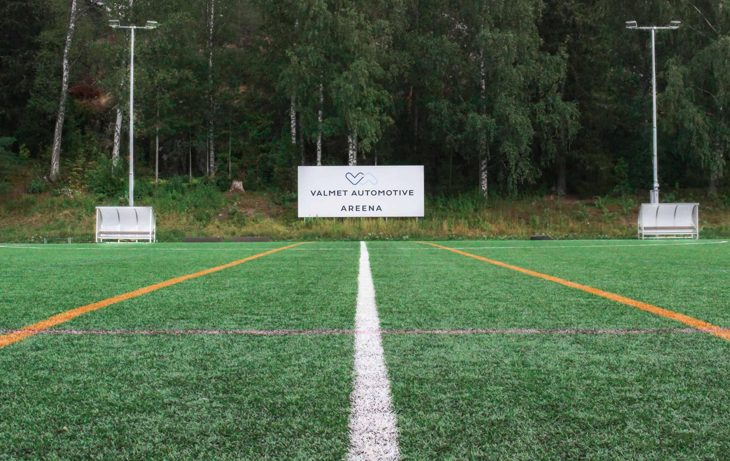 Jalkapallokenttä, jolla vaihtoaitiot, nimikyltti ja led-valopylväät.