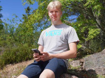 Juha Uggeldahl istuu kivellä älypuhelin kädessään.