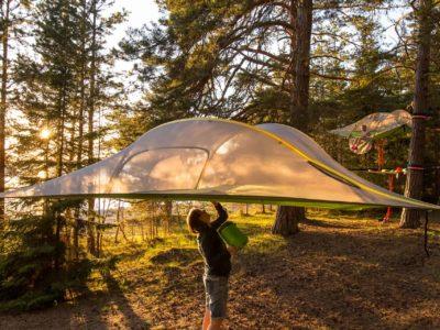 Leijuva Tentsile-teltta ja henkilö avaamassa teltan alapinnassa sijaitsevaa ovea.