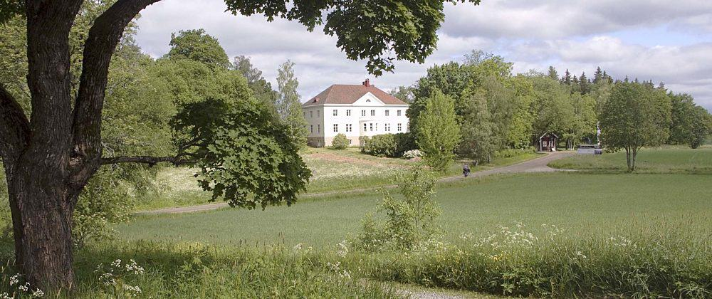Valkoinen rakennus peltomaisemassa.