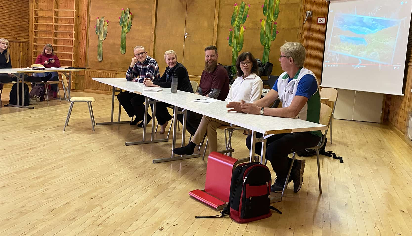Viisi ihmistä istuu pöydän ääressä.