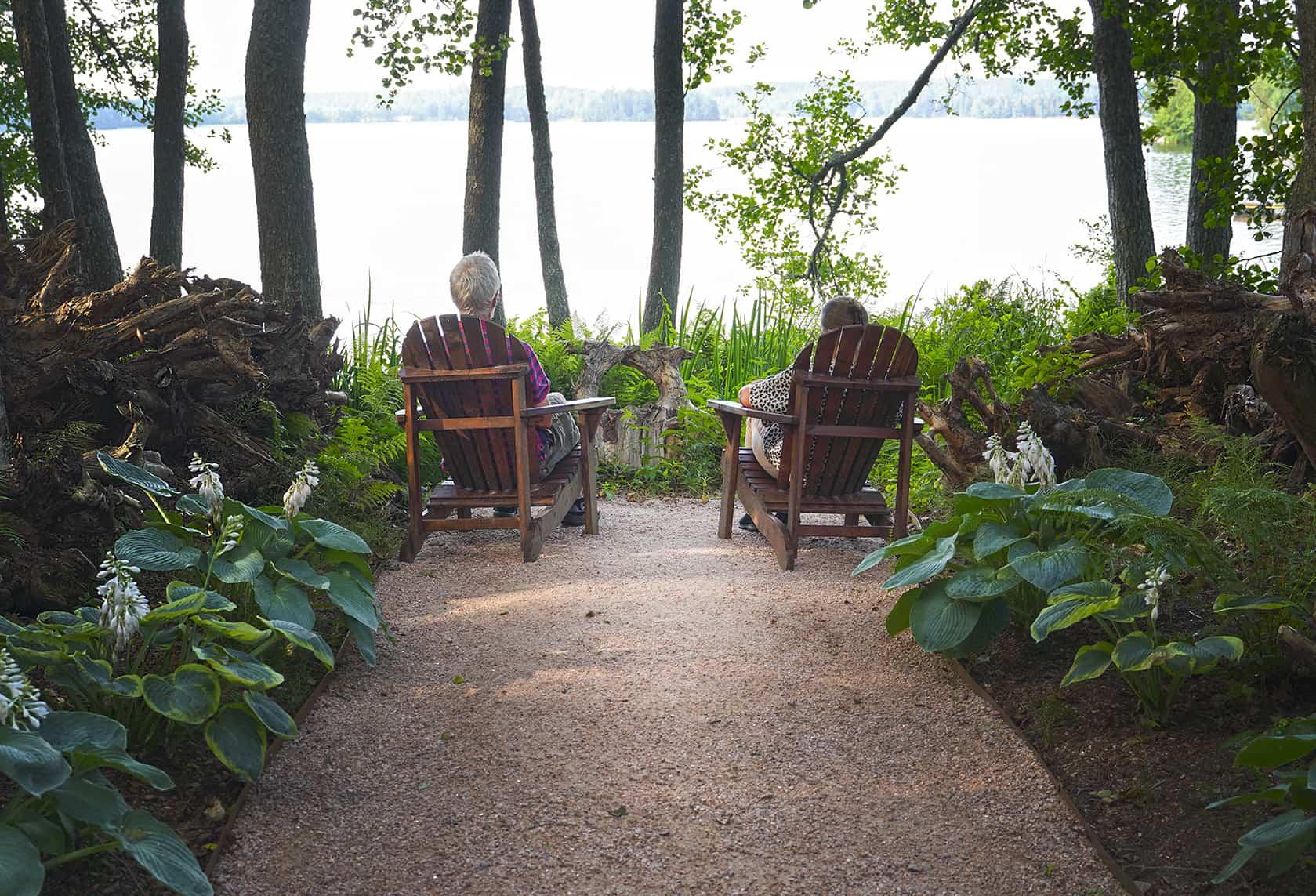 Pariskunta istuu puutarhatuoleilla katselemassa kohti Lohjanjärveä. Heidän vieressään näkyy kantoja ja polun varrella kuuliljoja.