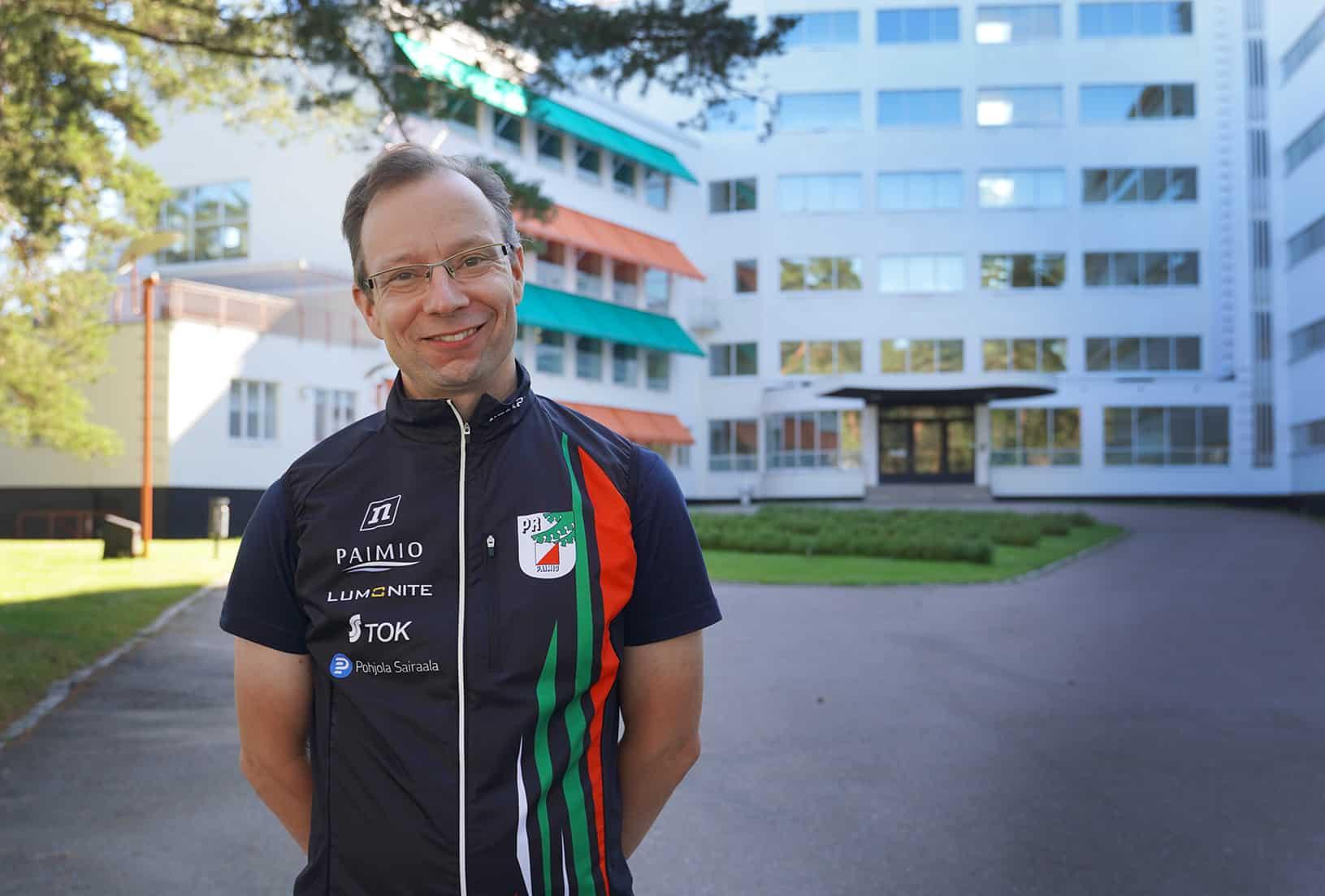 Etualalla Pertti Arola Paimion Rastin paidassa ja takana parantolan julkisivu.