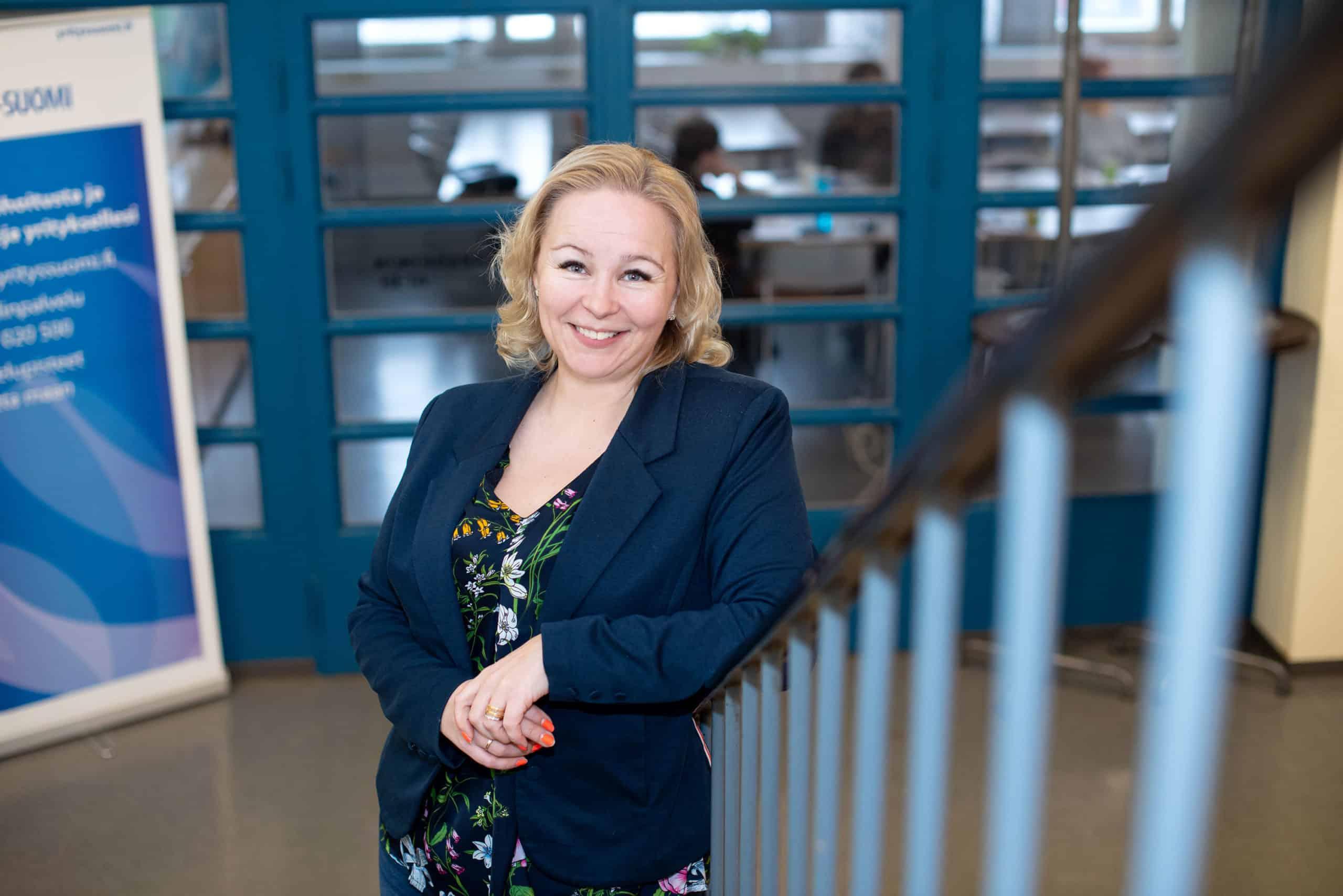 Heidi Loukiainen nojaa porraskaiteeseen toimistoympäristössä.