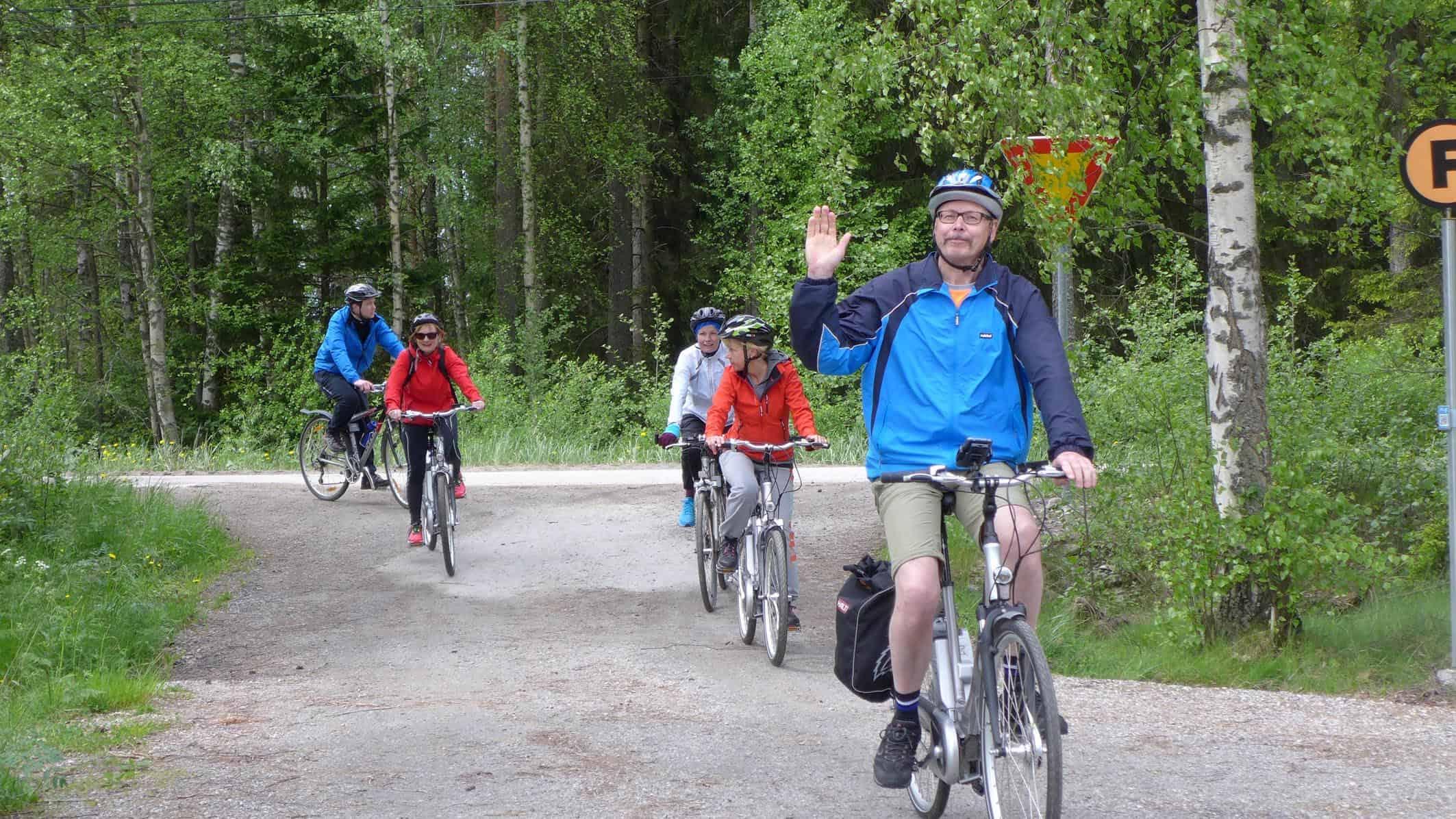 Viisi pyöräilijää, joista ensimmäinen vilkuttaa.