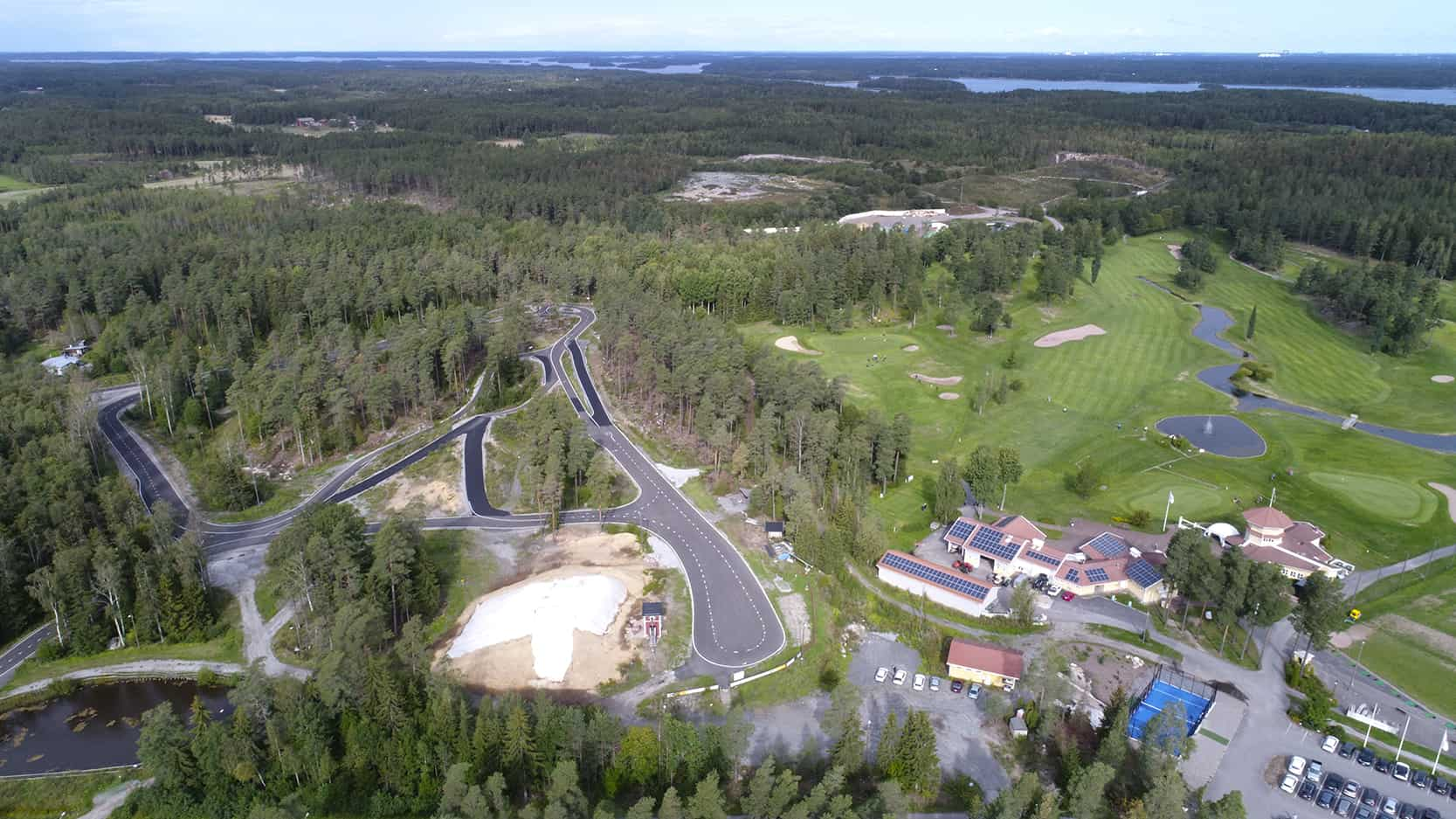 Ilmakuvassa näkyy vasemmalla rullahiihtorata ja oikealla golfkenttä, väliin jää sinipohjainen padel-kenttä.