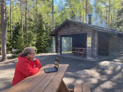 Taina Simola Kurjenrahkan kansallispuistossa. Takana näkyy nuotiopaikka.