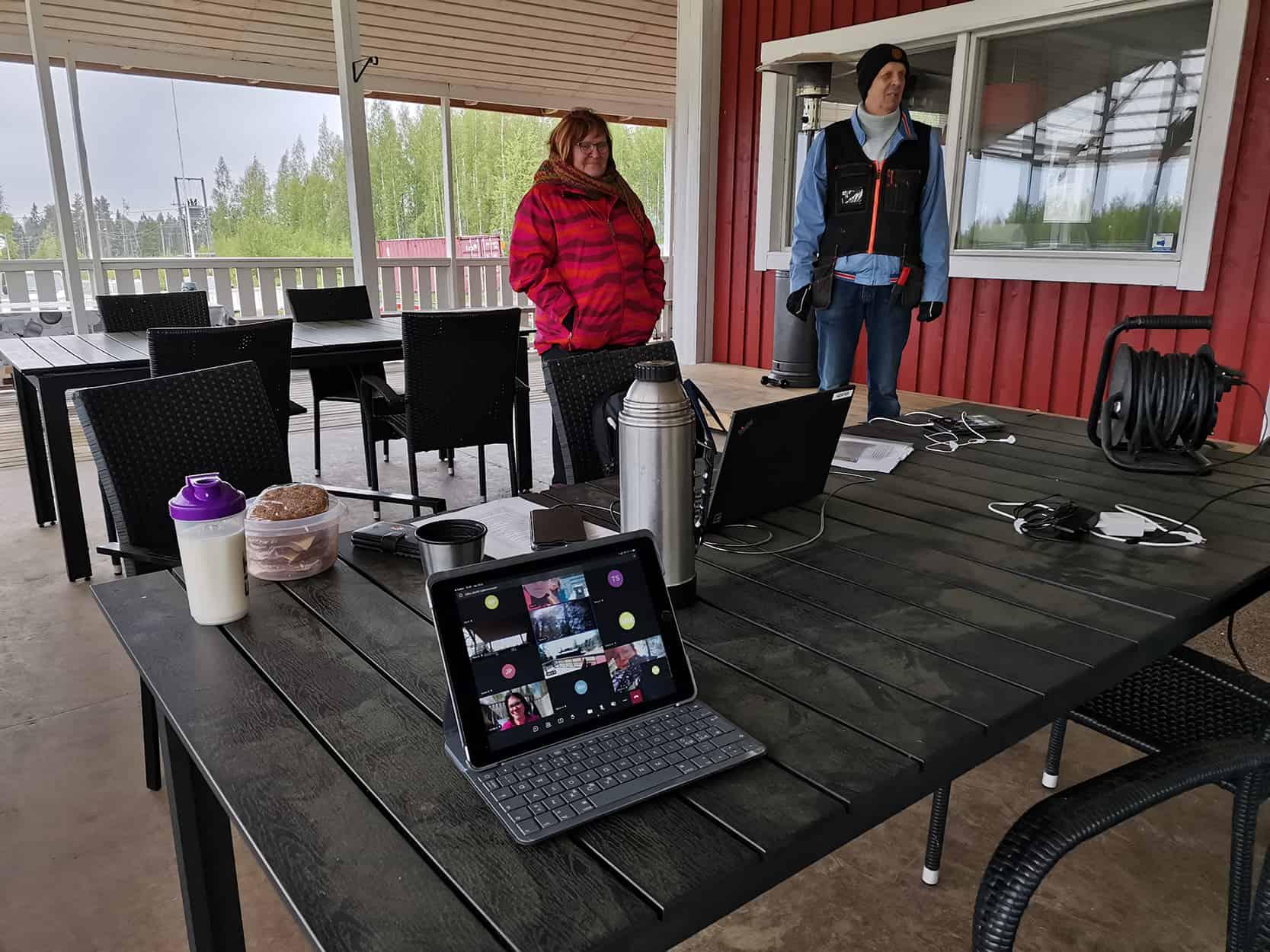 Kuvassa etualalla tietokone, jossa on auki Teams-kokous ja taka-alalla Päivi Kultalahti ja Heikki Salmela.