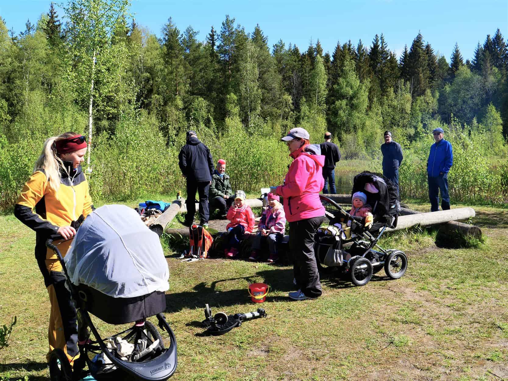 Kuva nuotiopaikalta, jossa on etätyöläisiä ja retkeilijöitä. Etualalla nainen lastenvaunujen kanssa.