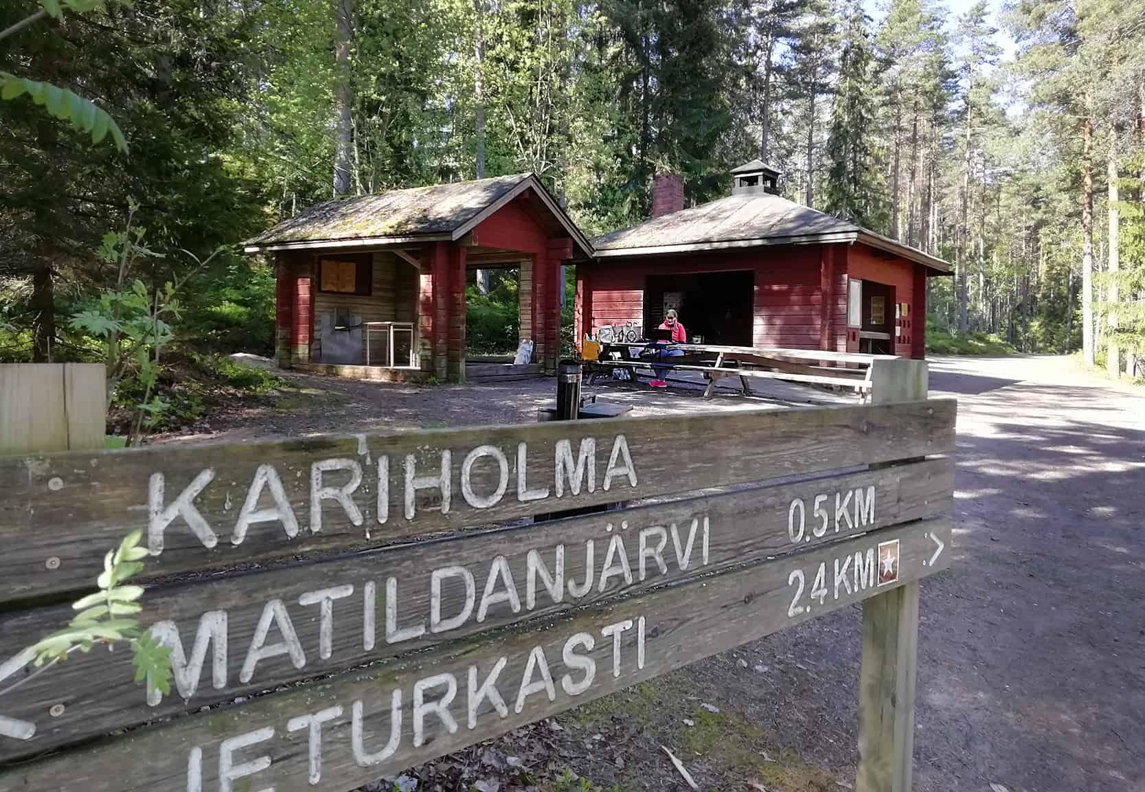 Kuvassa etualalla Kariholman opaskyltti ja taustalla Anu Pekanniemi tekemässä töitä tietokoneella.