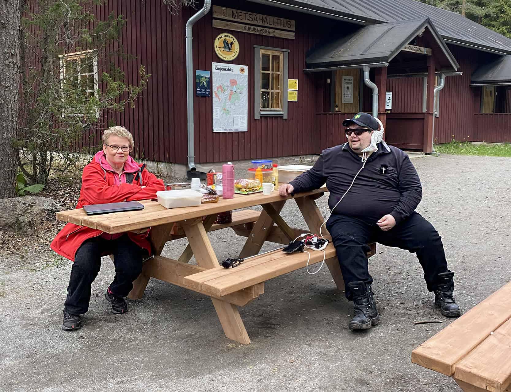 Kuvassa Taina Simola ja Kimmo Gustafsson istumassa pirttipöydässä Kurjenpesän pihalla.