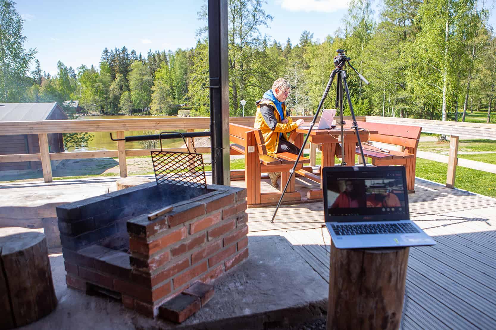 Kuvassa etualalla tietokone ja grilli. Takana Rauni Halonen istuu tietokoneella.