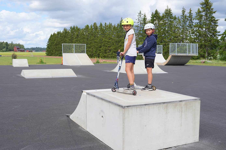 Kaksi lasta potkulautojen kanssa skeittirampin päällä.