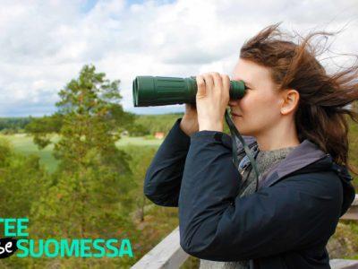 """Nainen katsoo kiikareilla maisemaa ja kuvan alareunassa lukee """"Tee se Suomessa""""."""