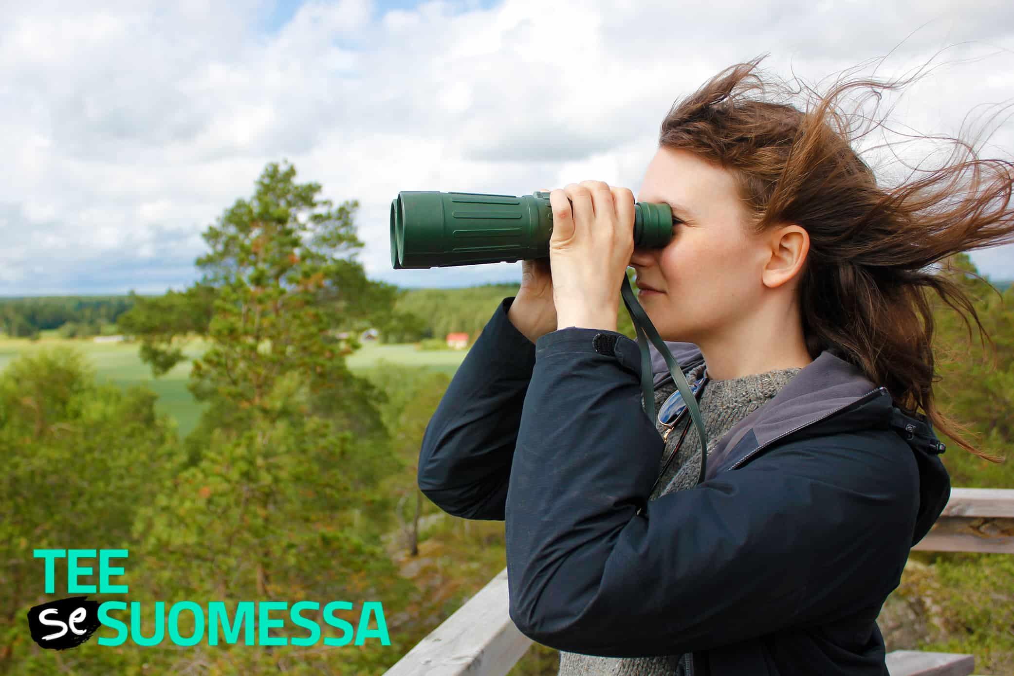 Nainen katsoo kiikareilla maisemaa ja kuvan alareunassa lukee