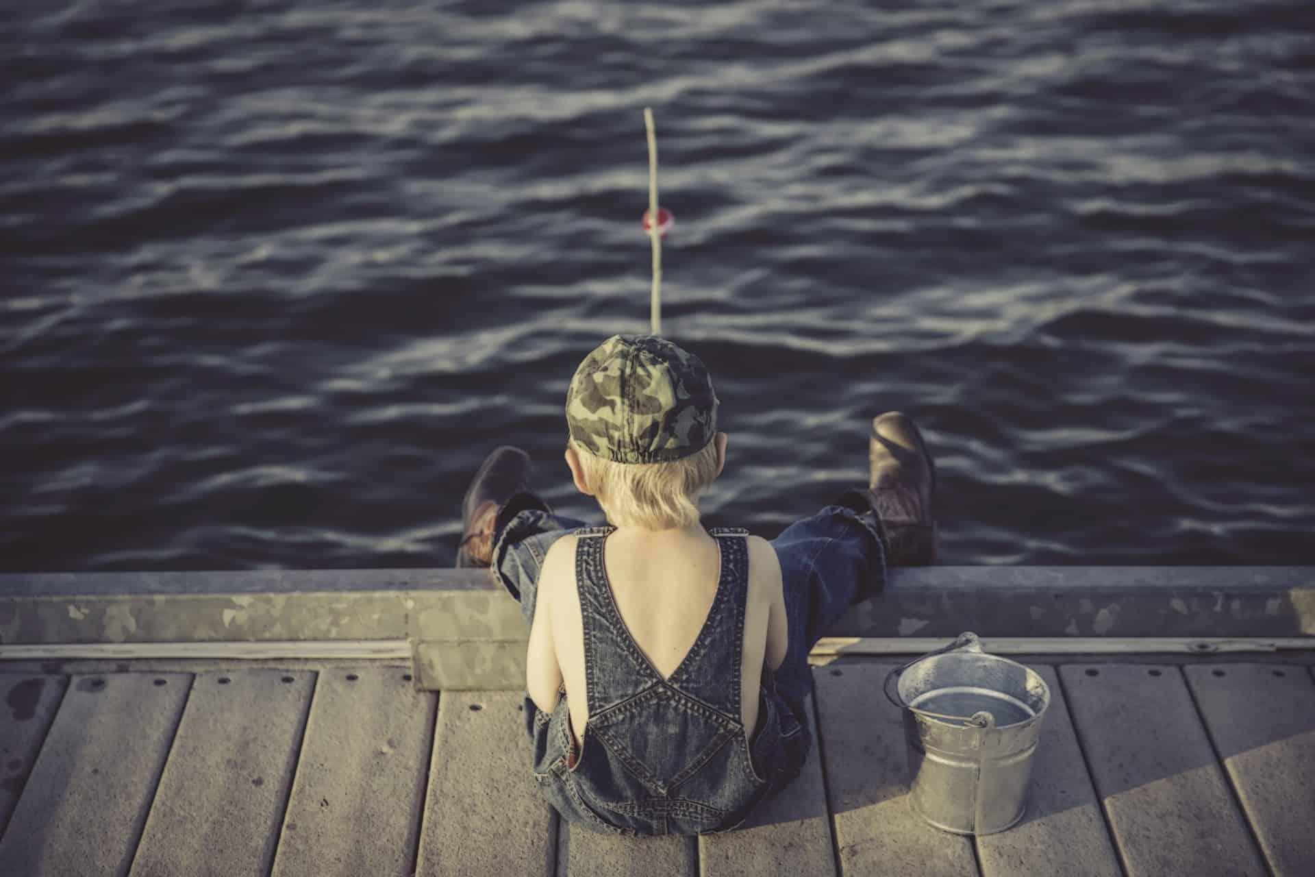 Lapsi istuu selin laiturilla ja kalastaa.