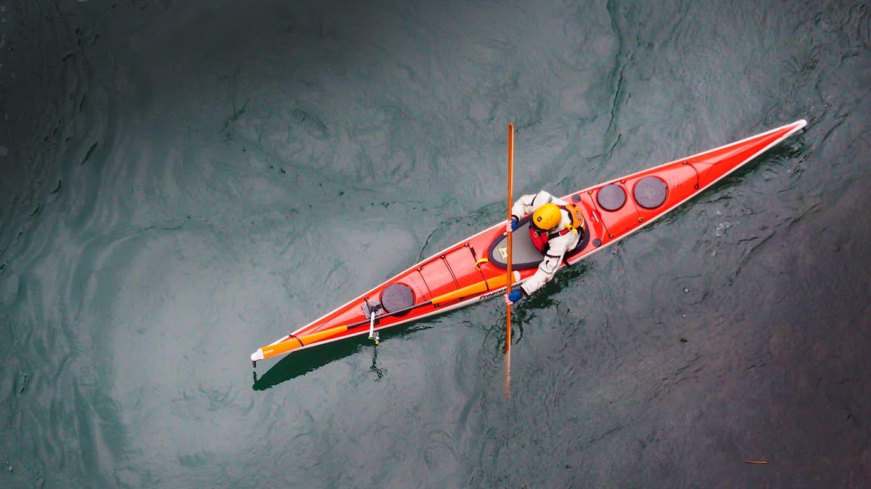 Punainen kajakki ja meloja merellä.