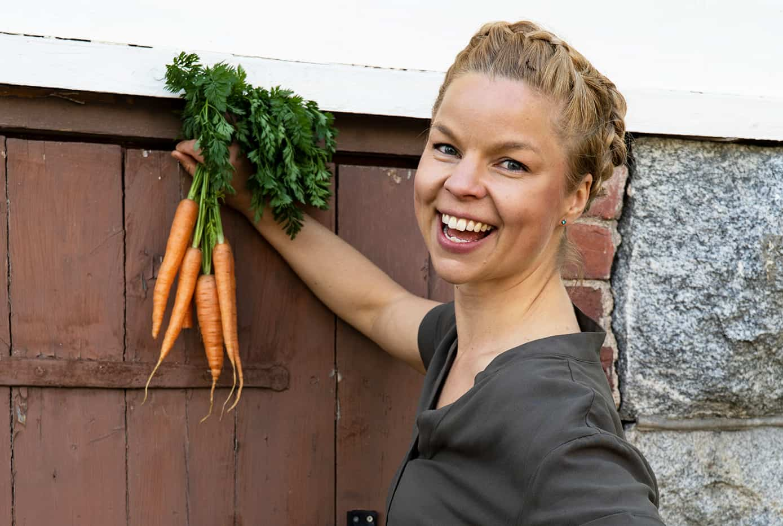 Henkilö pitelee porkkananippua kädessään.