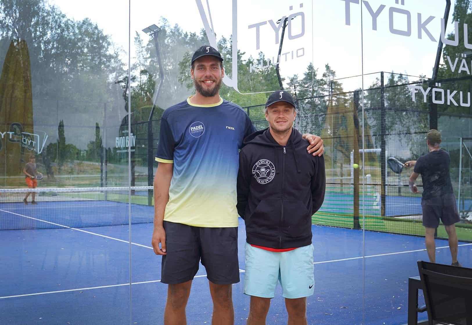 Mikeael ja Georg seisovat vierekkäin Pade Uusikaupunki Oy:n paidoissa padel-kenttien edessä.