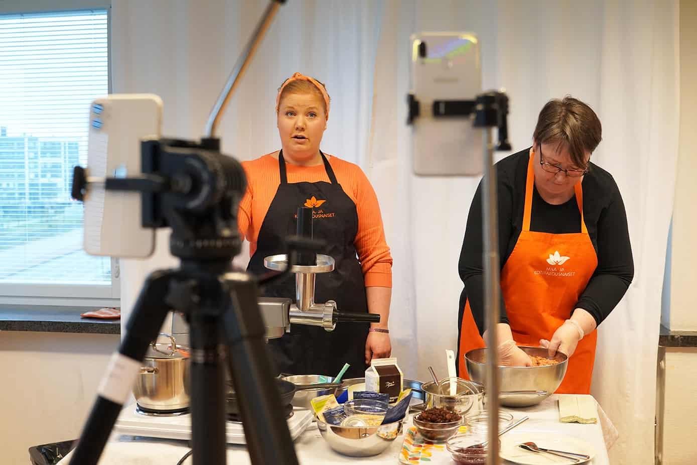 Janita Kylänpää ja Mari Mäenpää valmistavat rusinamakkaraa kameroiden takana.