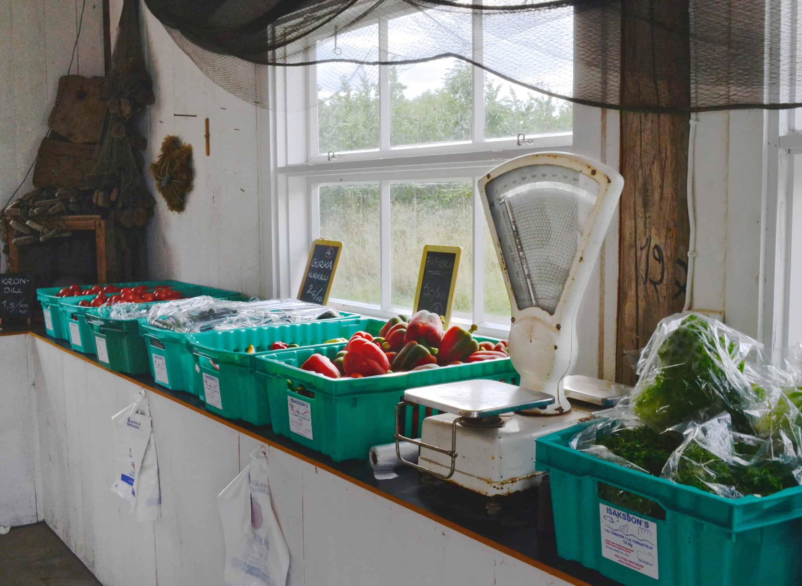 Hedelmä- ja vihanneslaatikoita sekä vaaka vanhassa rakennuksessa.